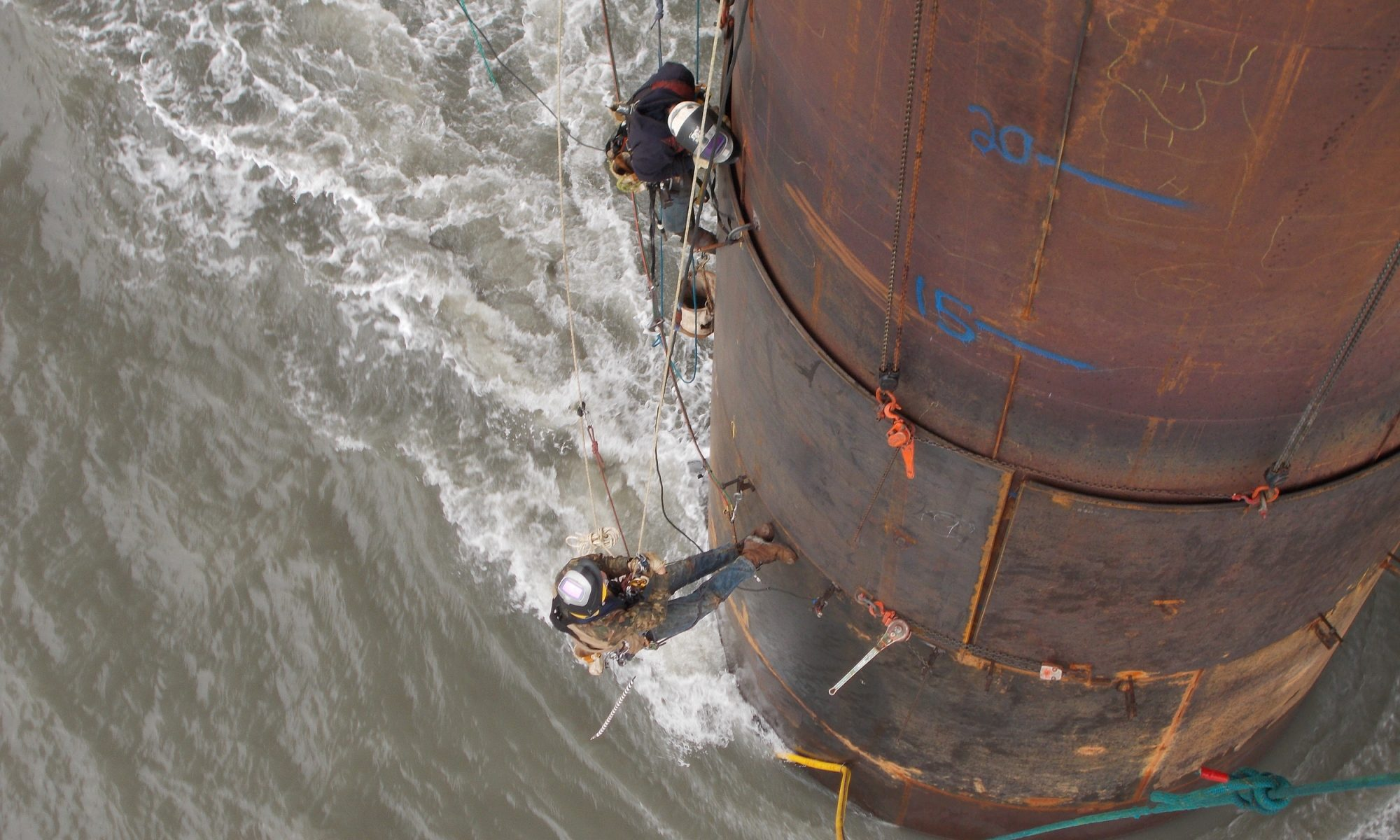 A pair of rope access technicians work along side an offshore oil rig easily in an otherwise difficult to reach area.