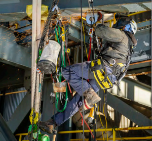 Rope access welding and pipe retrofit project, technician at work.