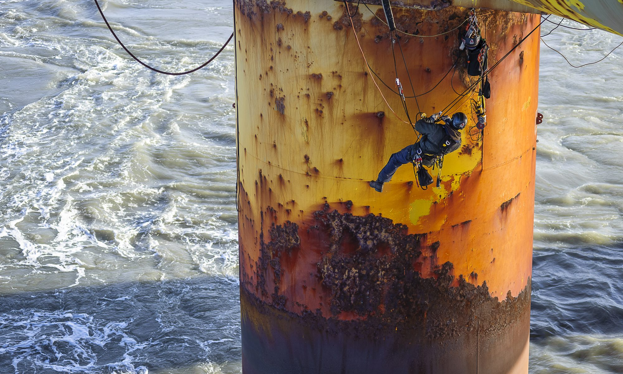 Team of rope access specialists work at height over ocean on offshore oil rig.