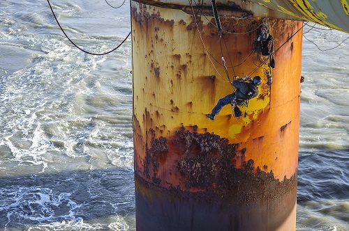Rope access technician scales down the side of offshore oil rig to access area for repair.