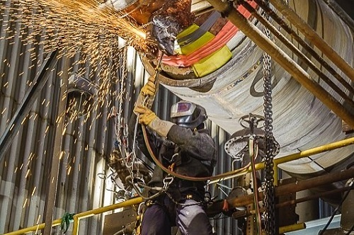 Certified welder in action underneath factor pipes at height utilizing rope access.