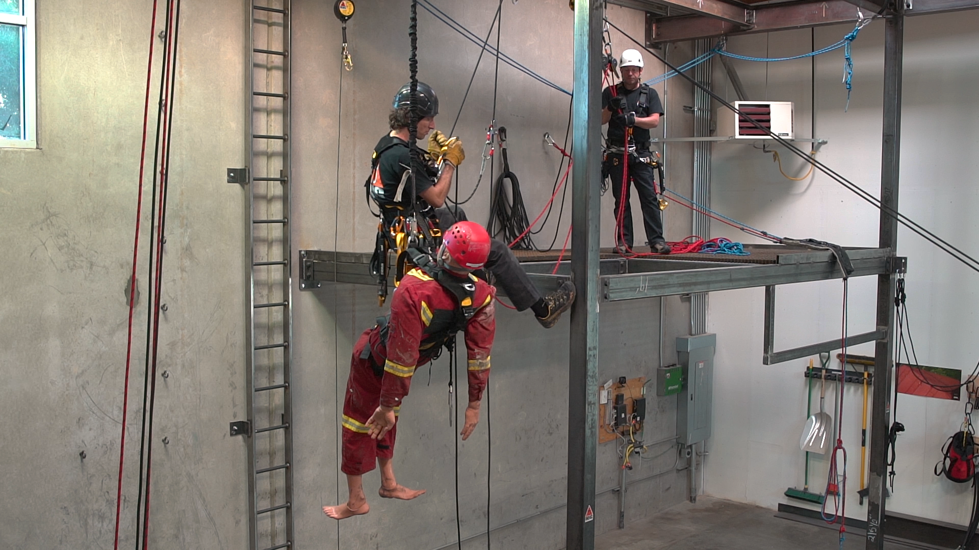 Training student works with a rescue dummy at height in RIG rope access training facility.