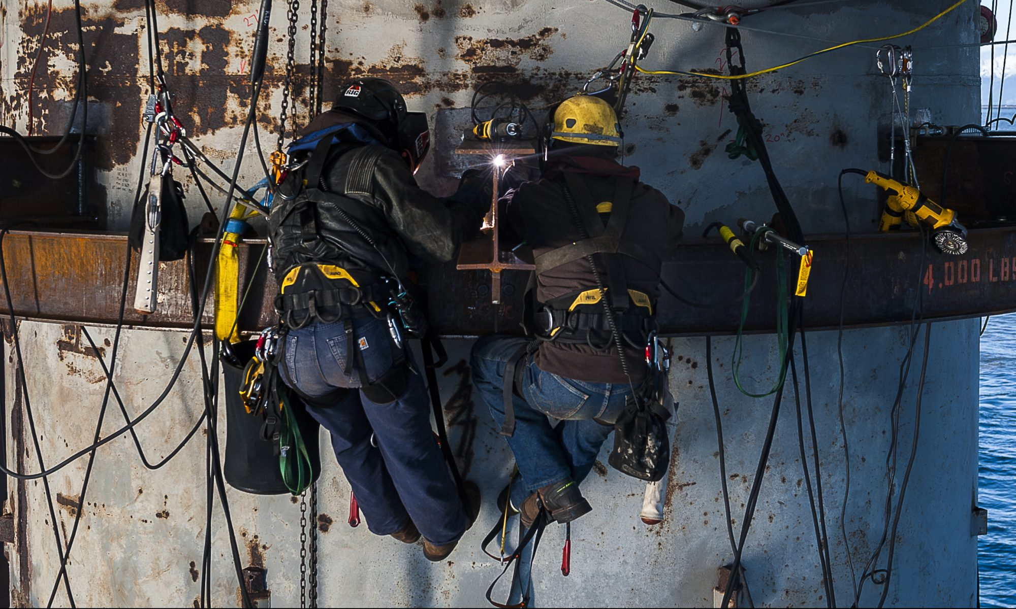 Two rope access technician stop to study plans along side an offshore oil refinery over 100 feet in the air.