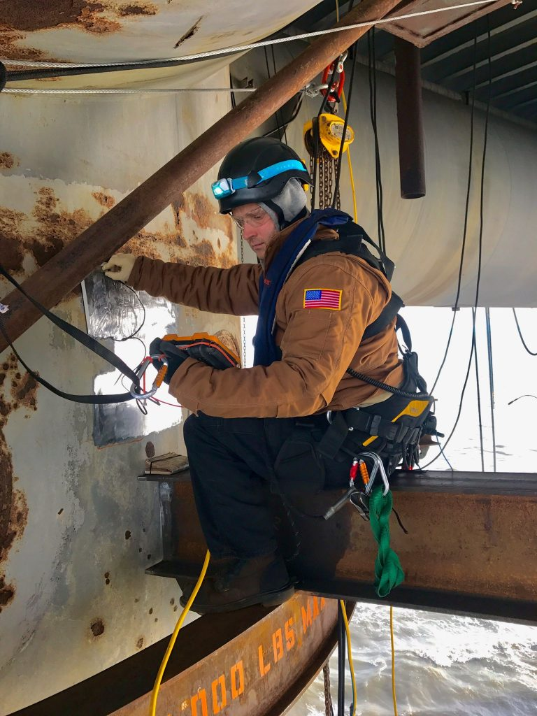 RIG technician performs inspection on oil rig at sea.