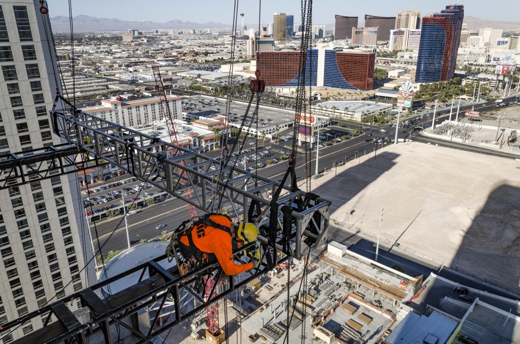 Rope access technician works on a rigging installation high above Las Vegas.