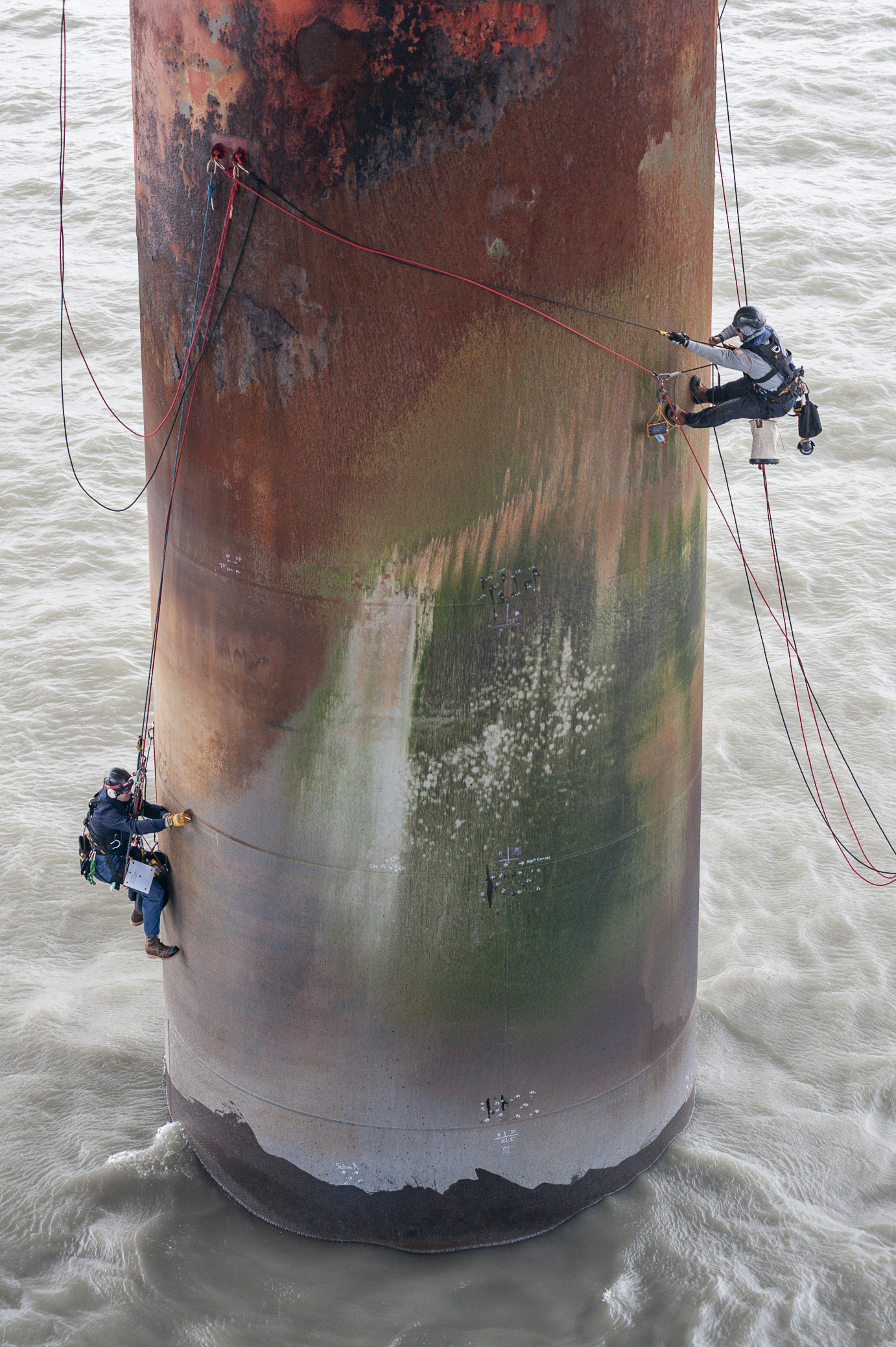 Two rope access technicians work on offshore oil rig.