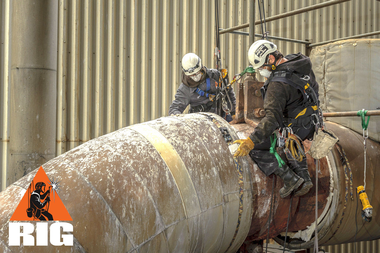 Rope access technician work on industrial pipe.